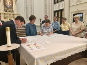Sister Janet Peterworth and Dr. Cindy Crabtree sign the lease transfer of all property on the Ursuline Campus to Sacred Heart Schools.